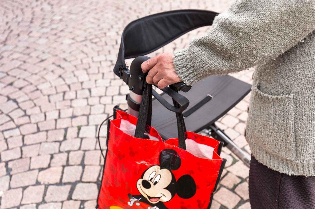 Frau mit Rollator und Mickey-Maus-Tasche